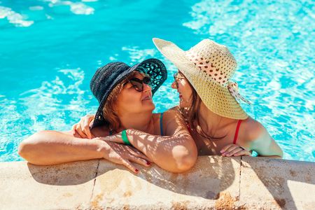 Senior woman relaxing with her adult daughter in hotel swimming pool. People enjoying summer vacation. Mother's day Archivio Fotografico