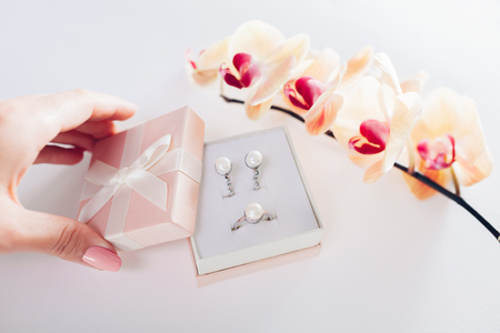 Woman opens a gift box with a set of perl jewellery with yellow orchid. Present for Valentine's day with flowers