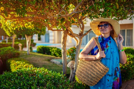Happy senior woman walking on hotel territory. Summer vacation. Stylish fashionable look