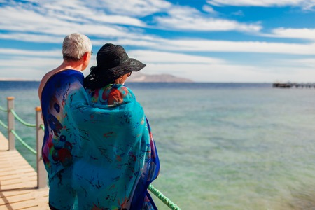 Senior couple walking on pier by Red sea covered with pareo. Happy people enjoying vacation. Valentine's day