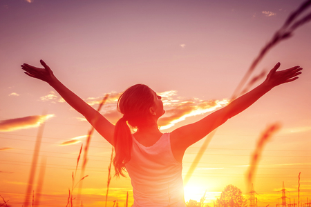 Free and happy woman raises arms against the sunset sky. Harmony and balance concept Imagens