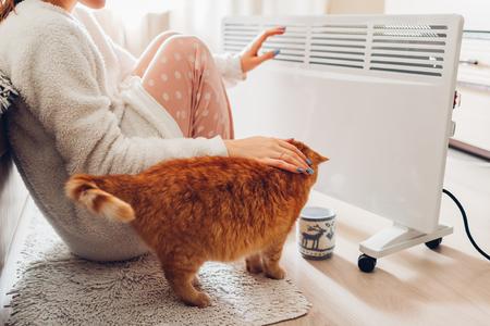 Używanie grzejnika w domu zimą. Kobieta grzejąca ręce, siedząca przy urządzeniu z kotem i nosząca ciepłe ubrania. Sezon grzewczy. Zdjęcie Seryjne