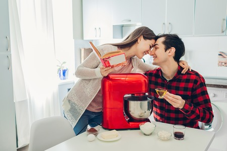 Young happy couple cooking on kitchen with food processor. Woman and man reading recipe and hugging. Lifestyle Фото со стока - 117964862