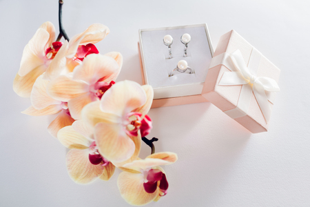 Woman opens a gift box with a set of perl jewellery with yellow orchid. Present for Womens day with flowers