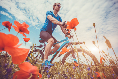 Young bicyclist rides on poppy field at sunset. Sport. Active lifestyle