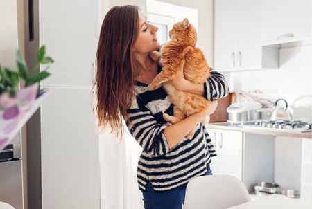 Young woman playing with cat in kitchen at home. Girl holding and hugging ginger cat. Happy master having fun with her pet
