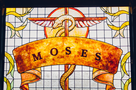 Moses painting on stained glass window. Brazen serpent on stick.