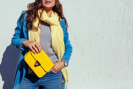 Young woman holding stylish yellow handbag and wearing trendy blue coat. Spring female clothes and accessories. Fashion