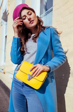 Mujer joven sosteniendo un elegante bolso amarillo y vistiendo un moderno abrigo azul. Primavera ropa femenina y accesorios. Moda Foto de archivo