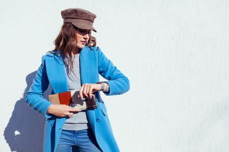 Junge Frau, die auf der Uhr schaut, eine stilvolle Handtasche hält und einen trendigen blauen Mantel und eine Mütze trägt. Frühlingskleidung und Accessoires für Frauen. Mode
