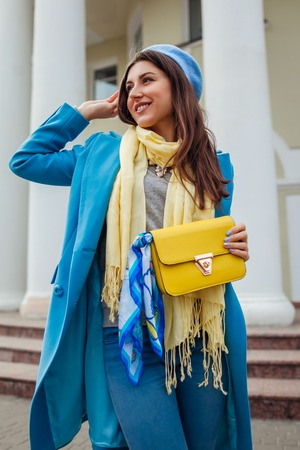 Young woman in trendy blue coat walking on city street holding stylish handbag. Spring female clothes and accessories. Fashion Banque d'images