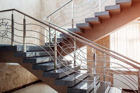 Treppenhaus im modernen Geschäftszentrumgebäude. Notevakuierungsausgang. Treppe im Einkaufszentrum. Weiße Leiter durch Fenster im Hotel. Stadtarchitektur.
