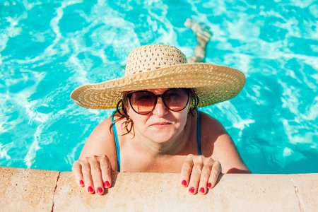 Senior woman in bikini relaxing in hotel swimming pool. People enjoying summer vacation. All inclusive