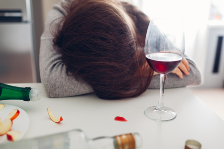 Female alcohol addiction. Young woman sleeping on kitchen table surrounded with wine bottles. Alcoholism Stockfoto