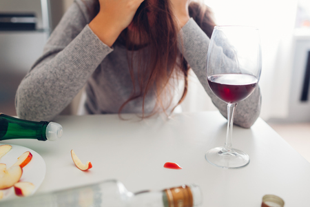 Female alcohol addiction. Young woman woke up on kitchen after party surrounded with wine bottles and having hangover