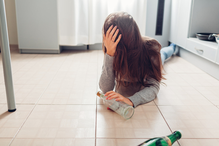 Female alcohol addiction. Young woman woke up on kitchen floor after party surrounded with wine bottles and having hangover Stockfoto