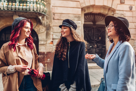 Outdoor shot of three stylish young women talking on city street. Happy girlfriends chatting and having fun