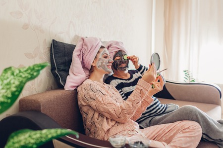 Mother and her adult daughter applying facial masks and tasting cucumbers looking at mirror. Women chilling and having fun at home sitting on couch
