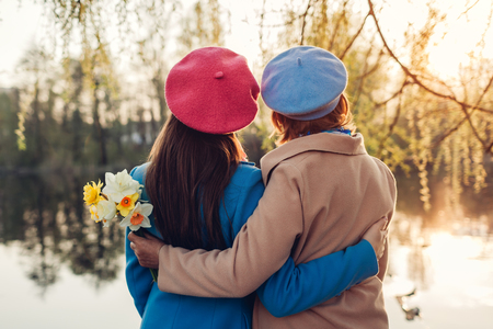 Happy senior mother with flowers and her adult daughter hugging by spring river at sunset. Mother's day concept. Family values