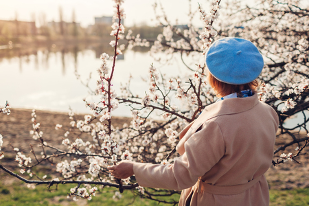 Senior woman relaxing in spring garden at sunset. Mothers day concept Imagens