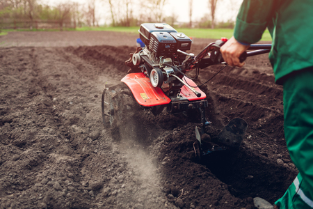 Farmer driving small tractor for soil cultivation and potato planting. Spring preparation. Agriculture