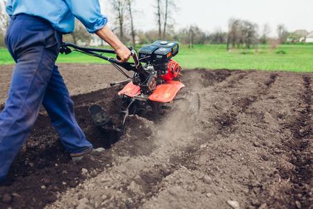 驾驶土壤耕种和土豆种植的小拖拉机的农夫。春天准备。农业