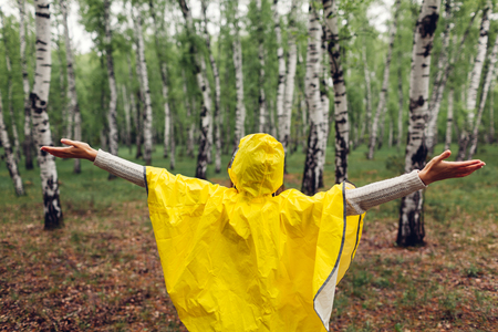 Happy young woman in yellow raincoat walking in spring forest under rain and having fun raising arms. Enjoying life