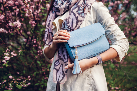 Young woman holding stylish blue handbag and wearing trendy outfit in garden. Spring female clothes and accessories. Fashion