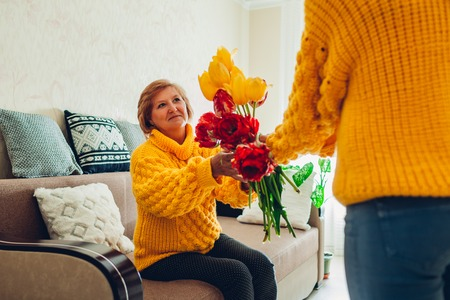 Daughter giving her mother bouquet of flowers at home. Mother's day gift Stockfoto
