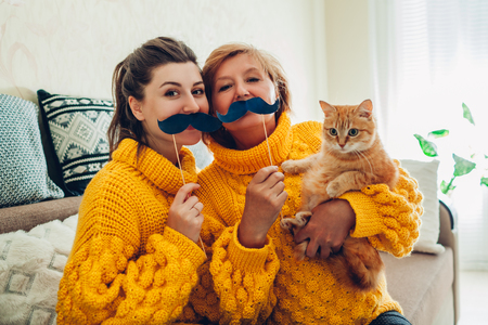 Senior mother and her adult daughter taking selfie with cat using photo booth props at home. Mothers day concept. Having fun Imagens
