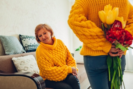 Adult daughter hiding flowers for mother behind her back at home. Mothers day present Imagens