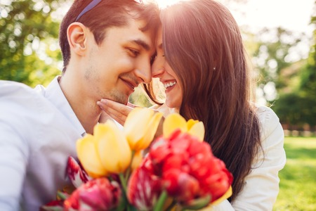Happy young couple in love hugging with spring flower bouquet outdoors. Man gifted his girlfriend with tulips 版權商用圖片