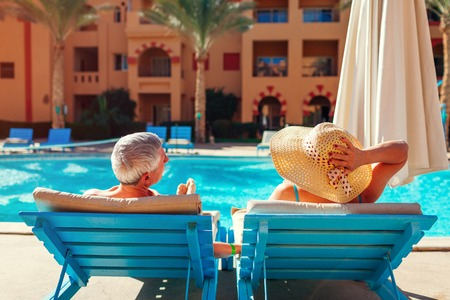 Senior family couple relaxing by swimming pool lying on chaise-longues. People enjoying summer vacation. Stockfoto