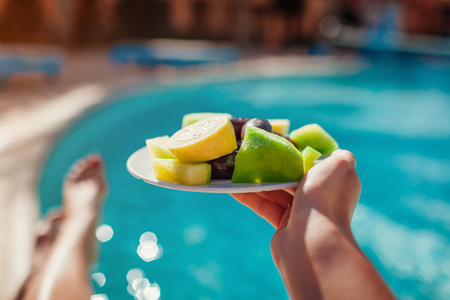 Woman holds plate with fruits on swimming pool background. All inclusive concept