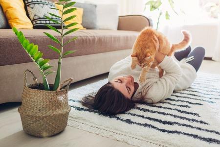 Jonge vrouw spelen met kat op tapijt thuis. Meester ligt op de vloer met haar huisdier en houdt kitten vast Stockfoto