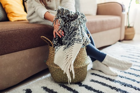 Young woman puts blanket in straw basket. Interior decor of living room. Reklamní fotografie