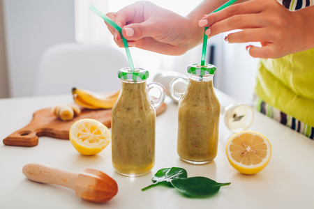 Bottles with spinach and banana smoothie with ingredients on kitchen table. Woman puts straws in drinks. Healthy detox diet