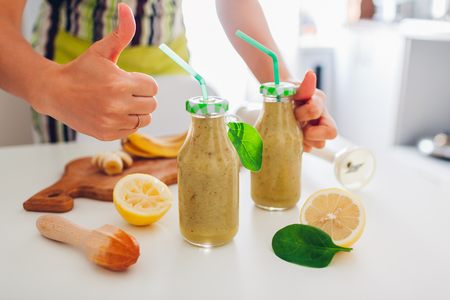 Bottles with spinach and banana smoothie with ingredients on kitchen table. Woman shows thumb up. Healthy detox diet