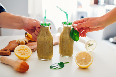 Bottles with spinach and banana smoothie with ingredients on kitchen table. People holding drinks. Healthy detox diet Reklamní fotografie