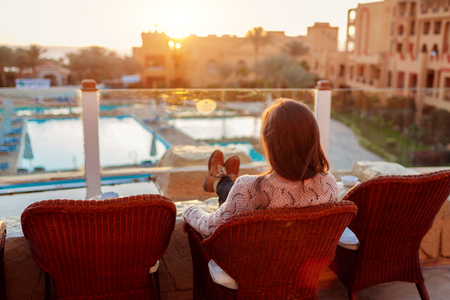 Woman relaxing at hotel balcony enjoying sunrise with swimming pool and sea view. Happy girl sitting on chair