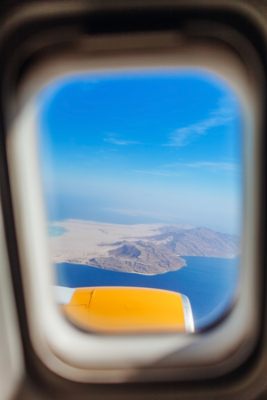 Plane window view of Egypt surrounded by sea and airplane through the window