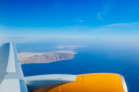 Plane window view of Egypt surrounded by sea, blue sky and airplane