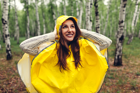 Happy young woman in yellow raincoat walking in spring forest under rain and having fun. Enjoying life