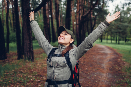 Happy woman tourist with backpack walking in spring forest and raising arms feeling free. Traveling and tourism concept Reklamní fotografie