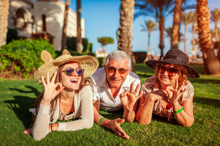 Senior couple lying on grass with adult daughter by hotel. Happy people enjoying summer vacation in Egypt. Family values Reklamní fotografie
