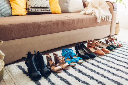 Choosing shoes at home. Hard choice to make from sandals, heels and flats of different styles and color. Fashion and shopping