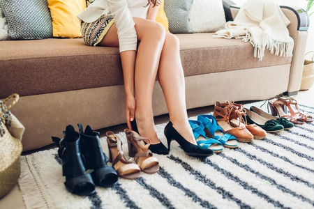 Young woman choosing shoes and trying them on at home. Hard choice to make from sandals, heels and flats. Female lifestyle Reklamní fotografie