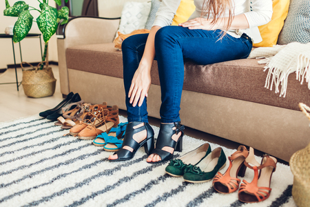 Young woman choosing summer shoes and trying them on at home. Hard choice to make from sandals, heels and flats. Fashion Reklamní fotografie
