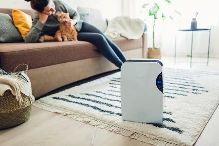Luftentfeuchter mit Touchpanel, Feuchtigkeitsanzeige, UV-Lampe, Luftionisator, Wasserbehälter funktioniert zu Hause, während Frau mit Katze spielt. Lufttrockner