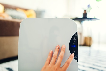 Woman turns dehumidifier on using touch panel at home. Modern airdryer device for cleaning air. Close up Reklamní fotografie
